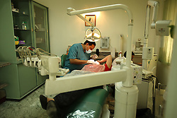 "Dr. Ala'a Al-Aswany, a prominent Egyptian writer and founding member of the political movement Kefaya, works on a patient in his dental office in Cairo, Egypt on April 4, 2008. ""My clinic is my window through which I can see what is happening in my society,"" said Al-Aswany. Trained as a dentist in Cairo and Chicago, Al-Aswany has contributed numerous articles to Egyptian newspapers on literature, politics, and social issues. His second novel, The Yacoubian Building, an ironic depiction of modern Egyptian society, has been widely read in Egypt and throughout the Middle East. It was translated into English and was adapted into a film (2006) and a television series (2007) of the same name. Chicago, Al-Aswany's latest novel, is set in the American city where he had attended college."