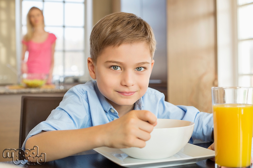 Portrait of boy having breakfast at table with mother standing in background