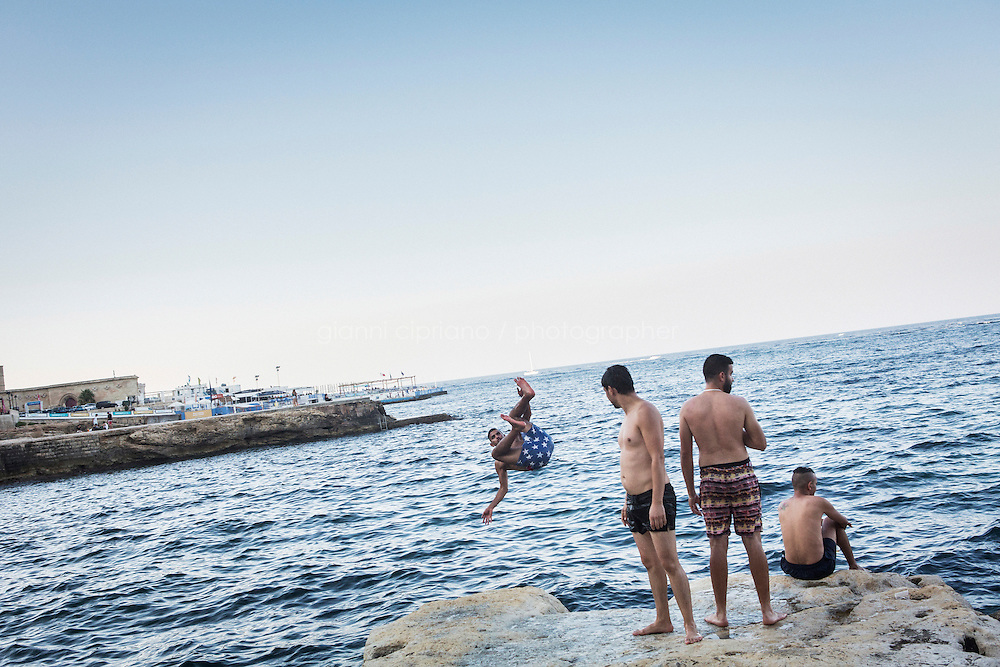 SLIEMA, MALTA - 28 AUGUST 2016: A young man dives into the sea in Sliema, Malta, on August 28th 2016.<br /> <br /> While many cities across the world denounce the defacing of a public property, on the Mediterranean island of Malta it is encouraged.<br /> <br /> According to Sandra Borg of Arts Council Malta, street art projects &ldquo;engage with numerous communities and contribute directly to urban regeneration&rdquo;. Funding from Arts Council Malta, allows schools to offer additional creative arts subjects and many choose street art; with &lsquo;NO WAR&rsquo; creator, James Grimaud, teaching students sketching, stencil making and aerosol use.