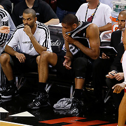 Jun 20, 2013; Miami, FL, USA; San Antonio Spurs point guard Tony Parker (left) and Tim Duncan (21) react on the bench against the Miami Heat during the first quarter of game seven in the 2013 NBA Finals at American Airlines Arena. Mandatory Credit: Derick E. Hingle-USA TODAY Sports