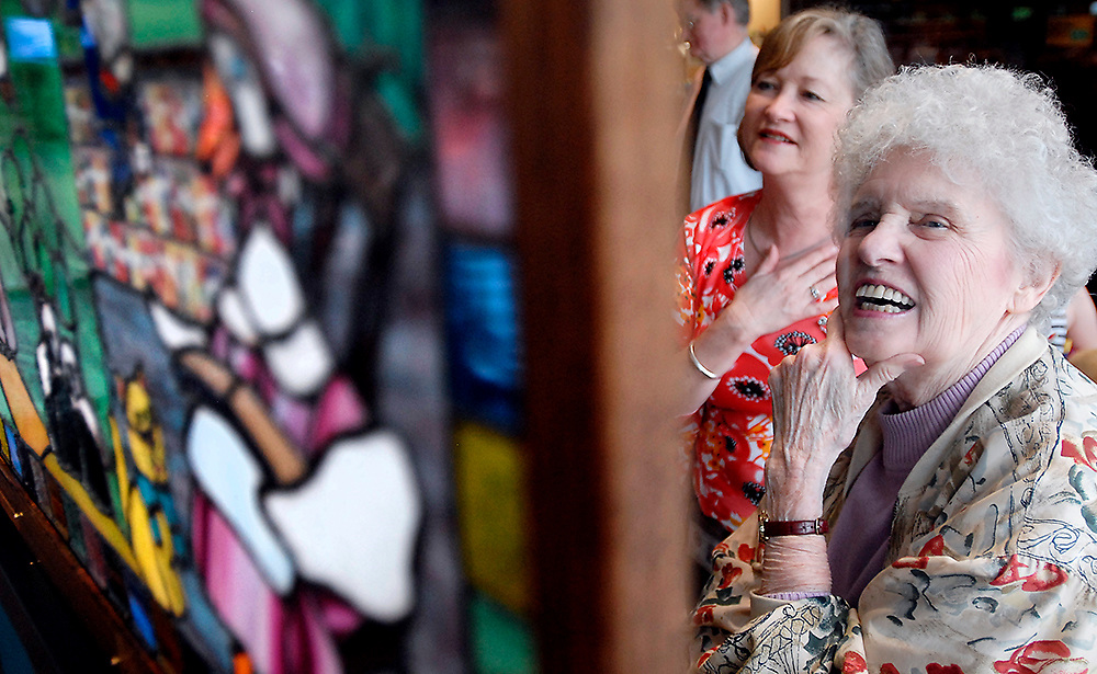 "Frances Reiher and Debbie King, from the right, admire a newly installed stained glass memorial at the Chantilly Regional Library on May 9. The memorial was designed for former librarian, Susan Woodcock who passed away in 2005 and worked as a children's librarian in the county system for 18 years. ""She was such a wonderful person,"" said Reiher who had worked with Woodcock as a librarian. The glass panels were designed by local artist, Jeanie Dunivin."