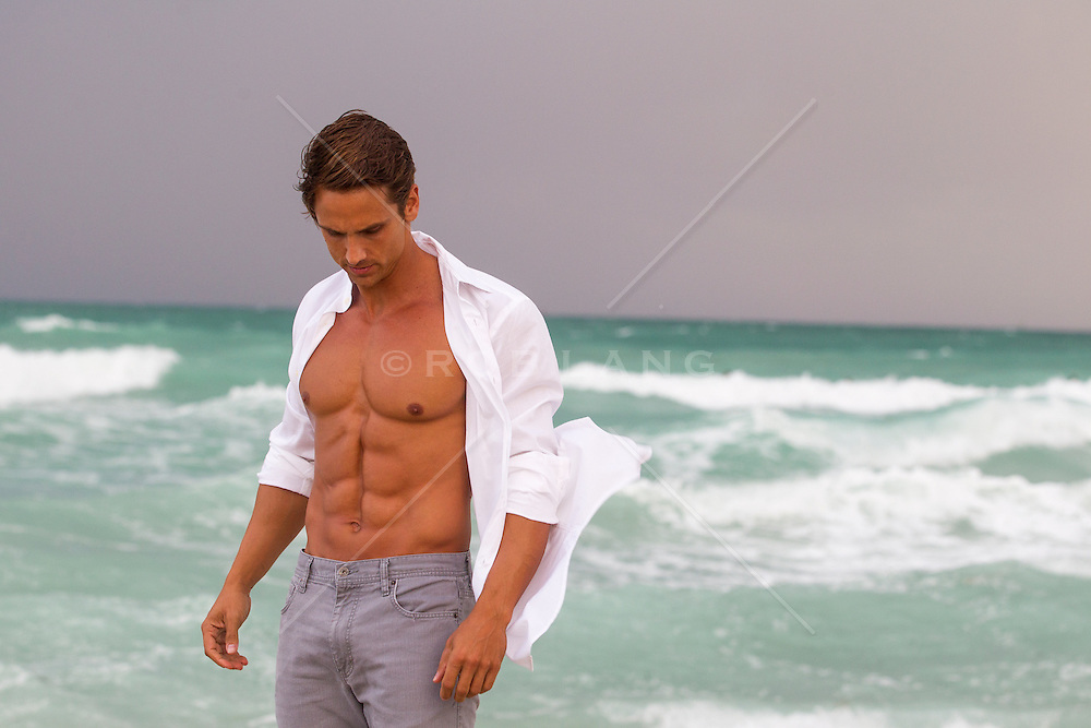 portrait of a very handsome muscular man with blue eyes and brown hair at the ocean with an open white shirt