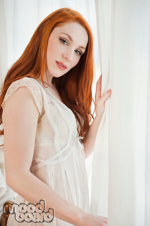 Portrait of young woman standing next to window holding curtain