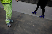 Legs of a woman wearing bright purple shoes walks fast past a workman's industrial boots along a London street
