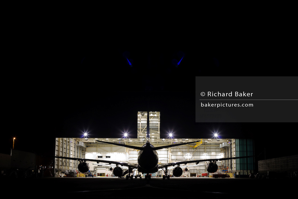 "In the darkness of a taxiway at the southern end of Heathrow Airport, the bright lights of an engineering hangar spill out into the night. A Boeing 747 Jumbo jet sits nose-in behind another during a scheduled set of maintenance tasks that every aircraft needs to keep to in order for its continued airworthiness. The unmistakable shape of this large aircraft is a half-silhouette against the intensity of the hangar and blue flare spots that arise from the internal glass in the camera's lens. From writer Alain de Botton's book project ""A Week at the Airport: A Heathrow Diary"" (2009). ."