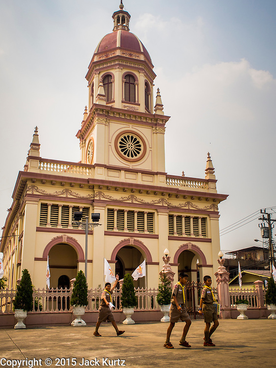 11 FEBRUARY 2015 - BANGKOK, THAILAND: Thai Boy Scouts walk past the Santa Cruz Catholic Church in the Thonburi section of Bangkok. There has been a Catholic church on the site since 1770. The current church was finished in 1916. It is one of the oldest Catholic churches in Thailand. Now the neighborhood around the church is known for the Thai adaptation of Portuguese cakes baked in the neighborhood. Several hundred Siamese (Thai) Buddhists converted to Catholicism in the 1770s. Some of the families started baking the cakes. When the Siamese Empire in Ayutthaya was sacked by the Burmese, the Portuguese and Thai Catholics fled to Thonburi, in what is now Bangkok. The Portuguese established a Catholic church near the new Siamese capital. There are still a large number of Thai Catholics living in the neighborhood around the church.     PHOTO BY JACK KURTZ