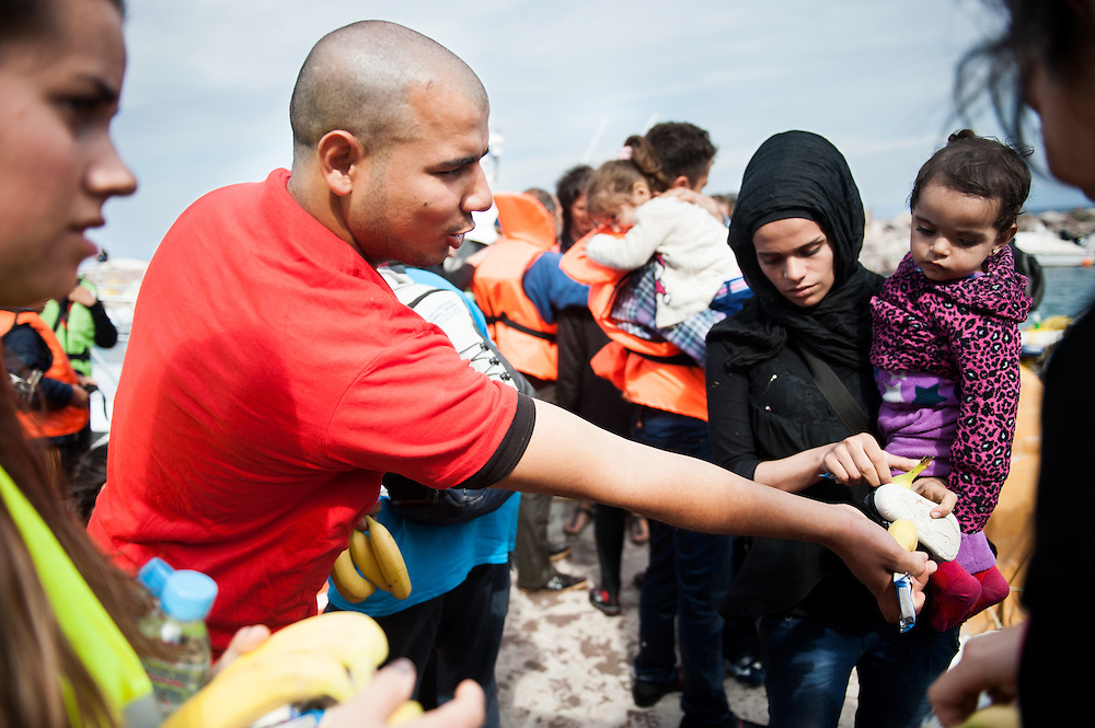 ActionAid's translator Moustafa hand food to a mother and her child who just arrived at Skala Sykamias, Lesvos, Greece.