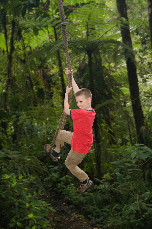 Boy (age 9) on rope swing in cloudforest, Sachatamia Lodge, Mindo, Pichincha province, Ecuador, South America.  MR