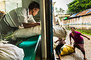 15 JUNE 2013 - YANGON, MYANMAR:  Yangon Circular Railway is the local commuter rail network that serves the Yangon metropolitan area. Operated by Myanmar Railways, the 45.9-kilometre (28.5mi) 39-station loop system connects satellite towns and suburban areas to the city. The railway has about 200 coaches, runs 20 times and sells 100,000 to 150,000 tickets daily. The loop, which takes about three hours to complete, is a popular for tourists to see a cross section of life in Yangon. The trains from 3:45 am to 10:15 pm daily. The cost of a ticket for a distance of 15 miles is ten kyats (~nine US cents), and that for over 15 miles is twenty kyats (~18 US cents). Foreigners pay 1 USD (Kyat not accepted), regardless of the length of the journey.     PHOTO BY JACK KURTZ