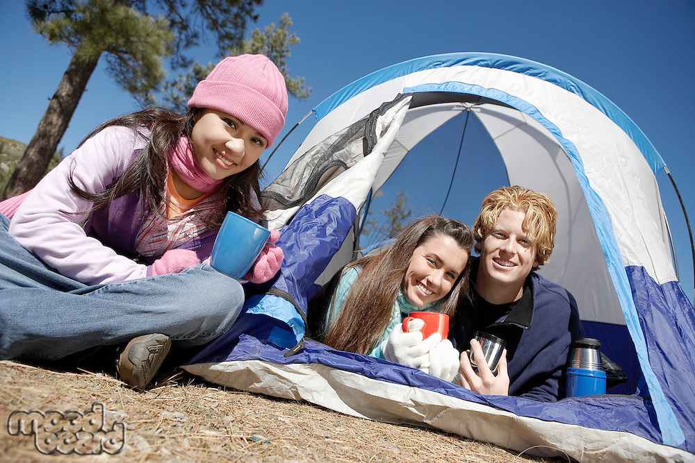 Three young adults at campsite by tent at campsite