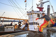Het lossen van de vangst van de afgelopen week. Sommige viskisten gaan rechtsreeks naar de vismarkt in de Visafslag. Rechtsreeks van de visser kopen kan soms ook.