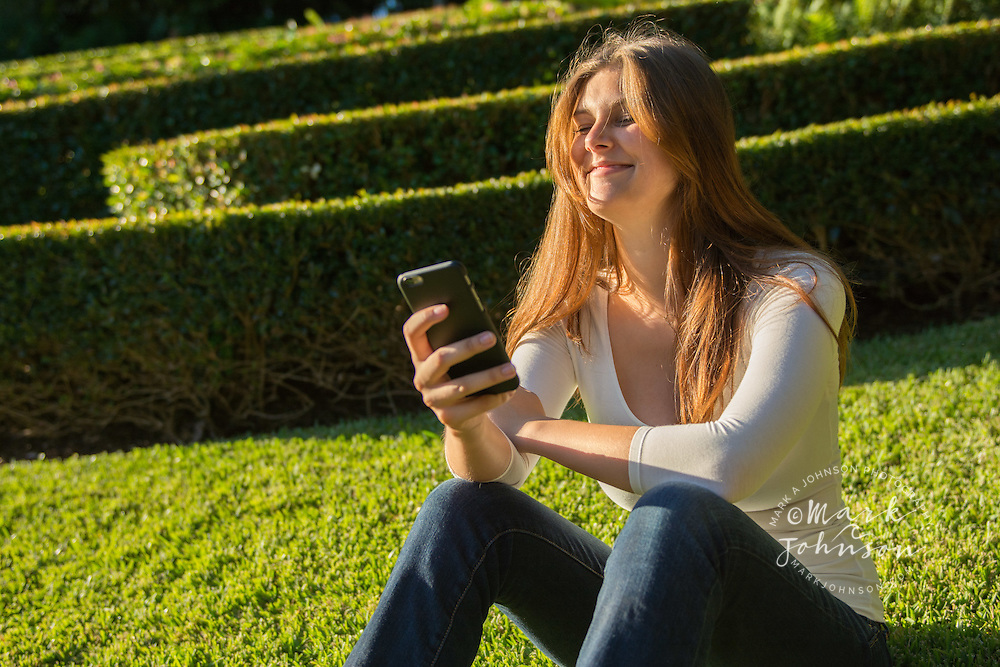 Young woman texting on a cell phone/mobile phone at Roma Street Parklands, Brisbane, Queensland, Australia