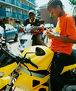 Young boy sitting on a yellow motorbike while another boy looks on and laughs Hackney London 2001.