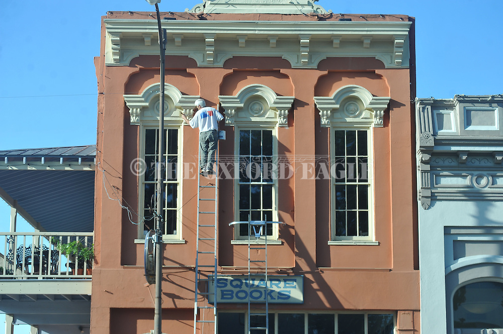 Scott Tidwell paints around the windows at Square Books in Oxford, Miss. on Tuesday, May 19, 2015.