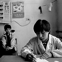 """IDONGLU, 11 MARCH 2001: a nun writes a diagnoses for a patient while his father looks on in an """"emergency """" station near the official catholic church in Donglu.China cut relations with the Vatican in the early fifites and since then, established a Patriotic catholic Church that's controlled by Chinese authorities.<br />Catholics who refused to give up their ties with the Vatican, started worshipping in underground churches and consequently were persecuted for a long time. Since the late nineties though, relations with the Vatican informally started to improve. Although China still has no diplomatic relations, many representatives from official churches met the pope John Paull II secretely . The Vatican, under the pope's leadership, has made several efforts to recover the tie with China. In February 2006 , Hong Kong Bishop Joseph Zen was named one of the first 15 new cardinals, which is seen by many as a gesture of goodwill and a significant step towards recovering the Vatican-China relationship."""
