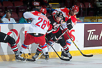 KELOWNA, CANADA - NOVEMBER 9: Brayden Point #19 of Team WHL digs for the puck between Daniil Vovchenko #28 and Kirill Ablaev #26 of Team Russia  on November 9, 2015 during game 1 of the Canada Russia Super Series at Prospera Place in Kelowna, British Columbia, Canada.  (Photo by Marissa Baecker/Western Hockey League)  *** Local Caption *** Brayden Point; Daniil Vovchenko; Kirill Ablaev;