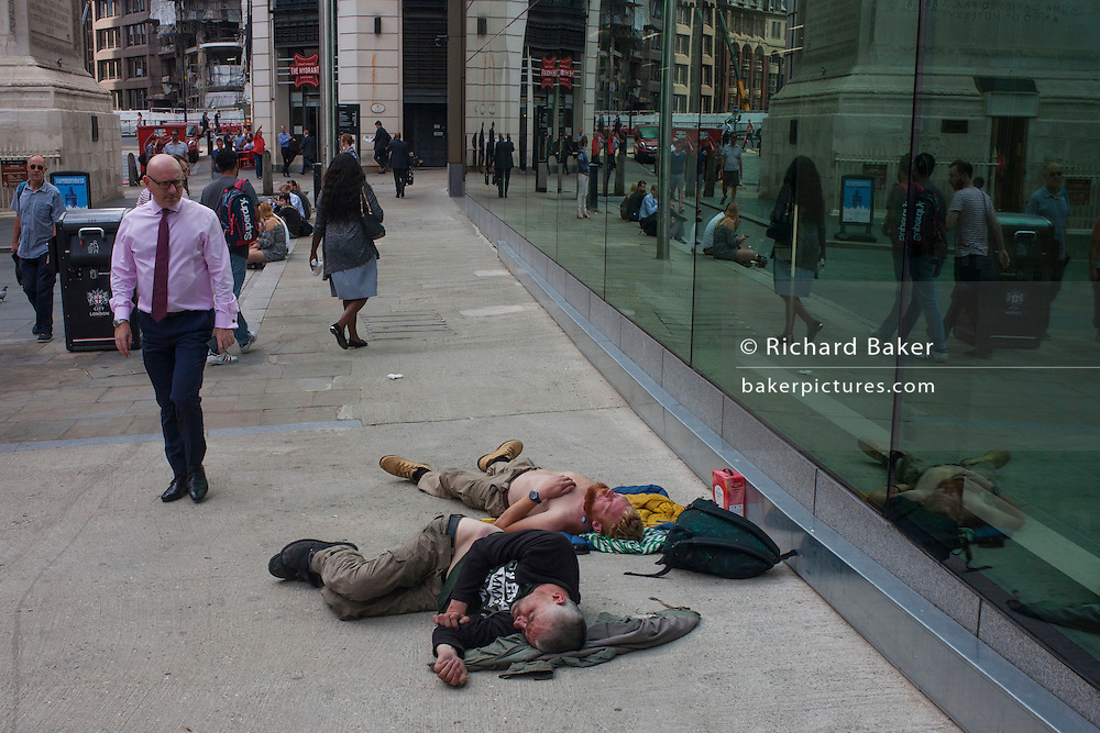 Two men sleep on the ground near Pudding lane, the location of the Great Fire of London (1666), on 13th September 2016, in the City of London, England.