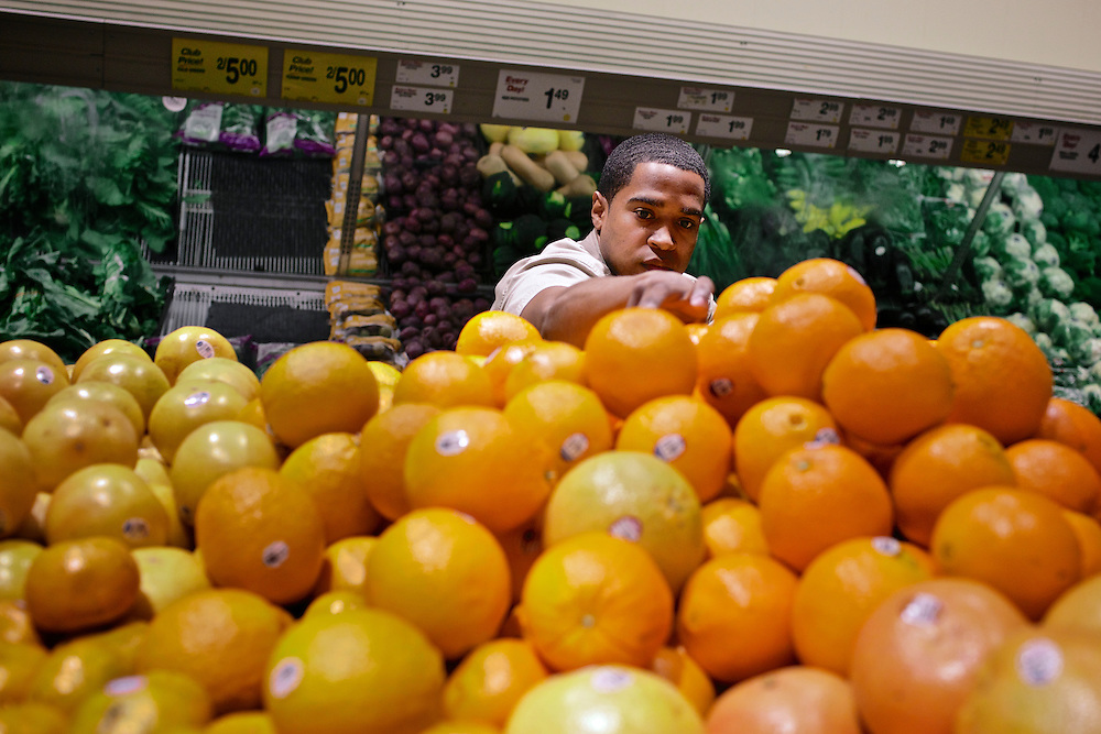 Elio Perdomo, restocks oranges in the produce section at a Safeway grocery store in Silver Sping, MD. Perdomo, a student at Montgomery College, tries to take classes in the morning and works up to 16 hours a week at the supermarket.