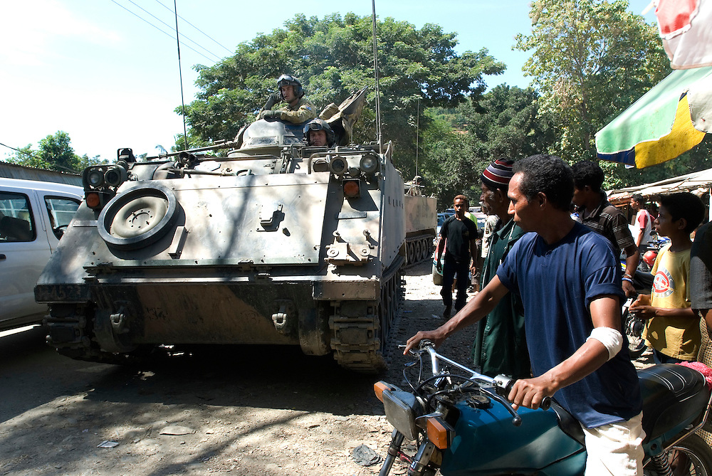 Locked in busy local traffic Australian Peace Keepers aboard Armoured Personal Carriers (APC) patrol Dili streets.