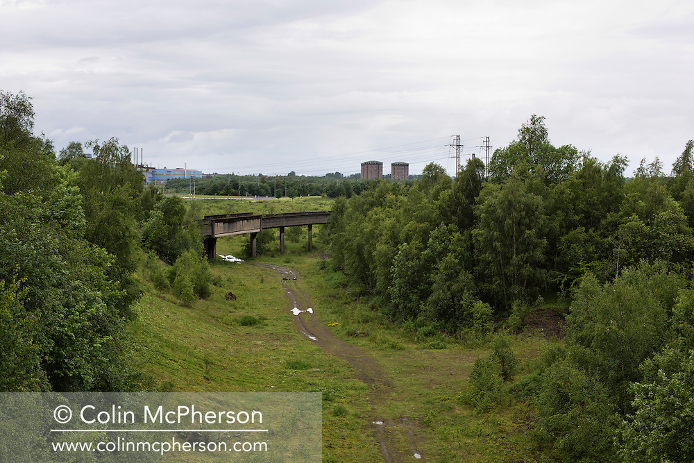'Untitled, 2014' from the project 'The Fall and Rise of Ravenscraig' by photographer Colin McPherson.<br /> <br /> The photograph shows a track through the site of the former steelworks at Ravenscraig.<br /> <br /> This project, photographed in 2014, looks at the topography of the post-industrial landscape at Ravenscraig, the site until its closure in 1992 of the largest hot strip steel mill in western Europe. In its current state, Ravenscraig is one of the largest derelict sites in Europe measuring over 1,125 acres (4.55 km2) in size, an area equivalent to 700 football pitches or twice the size of Monaco. It is currently being developed with a mix of housing, retail and the home of South Lanarkshire College and the Ravenscraig Regional Sports Facility.