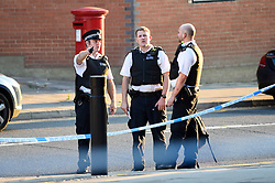 © Licensed to London News Pictures. 21/08/2018. LONDON, UK.  Police officers work behind a police cordon set up on Imperial Drive near Rayners Lane tube station, north west London, following a shooting in which two men suffered gunshot wounds.  It is reported that the suspect and accomplice have been.   Investigations are ongoing.  Photo credit: Stephen Chung/LNP