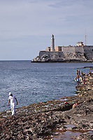 People relaxing and swimming along the Malecon in Havana, Cuba.
