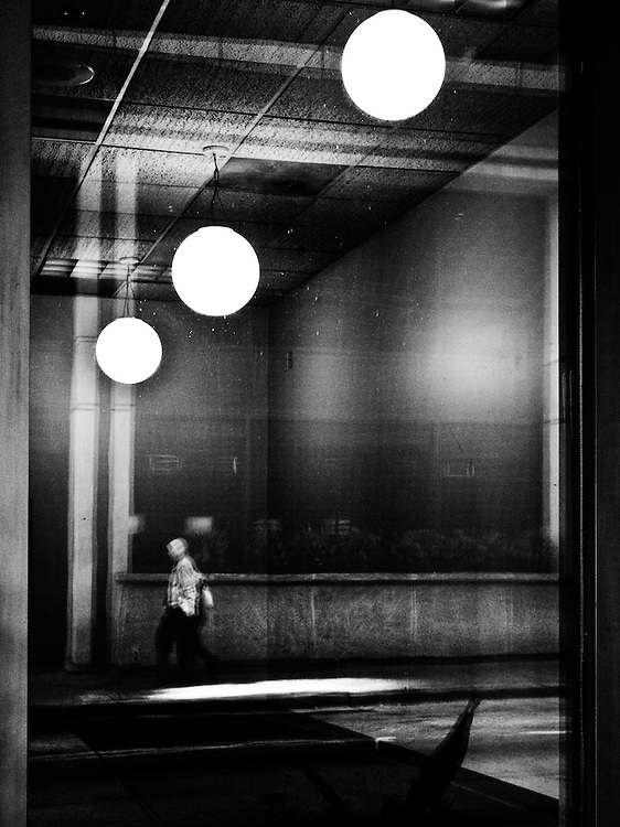 Photograph of an office buildings window with a reflection of a man walking down a city sidewalk.