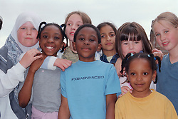 Multiracial group of primary school children standing together in playground,