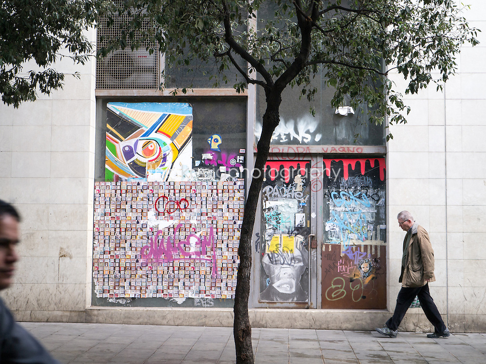 A man walks in front of graffiti/mural/street art in Barcelona, Spain.