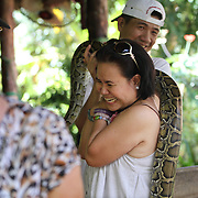 A tourist has a her picture taken with a snake in Ben Tre on the Mekong Delta, Vietnam.  Vietnam.  Photography by Jose More