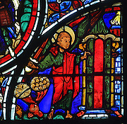 An angel with flaming sword closes the door of the Garden of Eden, which is red, however the wings of the angel and the door panel are green, the colour of hope, as God does not forsake man, from the stained glass window of the Parable of the Good Samaritan, 1215-25, in bay 13, in the ambulatory of Bourges Cathedral or the Cathedrale Saint-Etienne de Bourges, built 1195-1230 in French Gothic style and consecrated in 1324, in Bourges, Centre-Val de Loire, France. 22 of the original 25 medieval stained glass windows of the ambulatory have survived. The cathedral is listed as a UNESCO World Heritage Site. Picture by Manuel Cohen