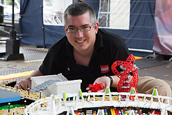 © Licensed to London News Pictures. 05/07/2012. London, UK. Warren Elsmore, the creator of a minature LEGO replica of the Olympic stadium and Orbit poses in front of his construction. Warren Elsmore used around 250,000 standard LEGO bricks to create a miniature replica of the London 2012 Olympic Games Park. The model took Warren, aged 35 from Edinburgh, 300 hours to construct and is on display at the 'Visit Denmark' Olympic Village  at St Katharine Docks, London. Photo credit : Vickie Flores/LNP