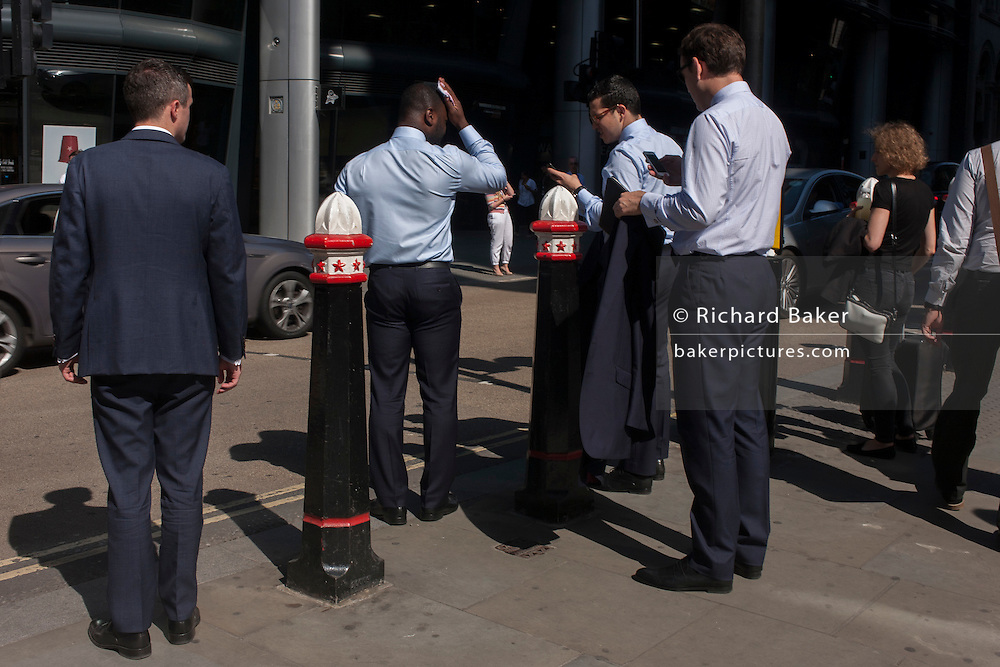 A businessman suffers from the heat during a heatwave on Cannon Street in the City of London, UK.