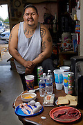 Louie Soto, a carpenter's assistant and tattooist, of Pima, Tohono O'odham, Mohawk, Ottawa, and Mexican heritage, with his typical day's worth of food while dieting at his old home in Sacaton, Arizona.  (From the book What I Eat: Around the World in 80 Diets.) The caloric value of his day's worth of food in May was 2,700 kcals. He is 30 years of age; 5 feet, 9 inches tall; and 320 pounds. MODEL RELEASED.