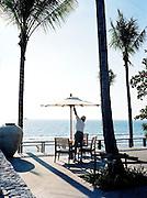 Hotel worker raises table umbrella at the 5-star Trisara Resort