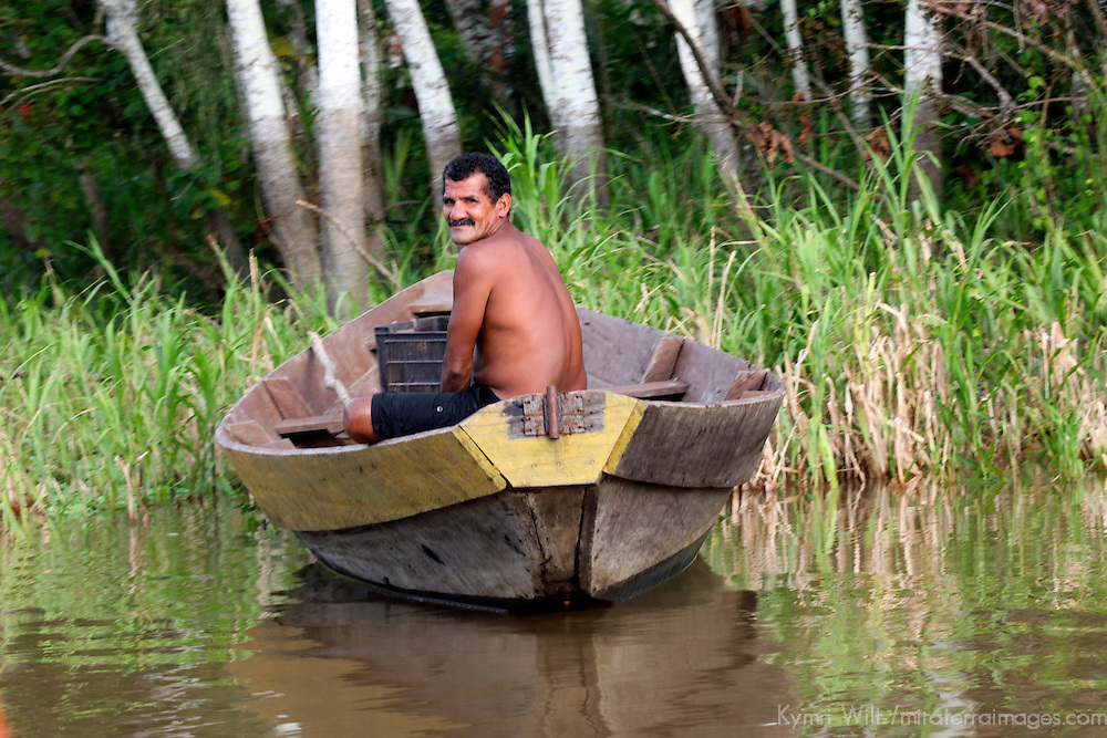South America, Brazil, Amazon.  A man smiles from his boat on the Amazon.