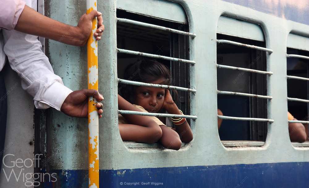 Girl stares from stationary train, Karnataka, India