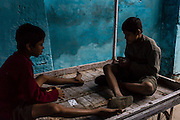 Two brothers playing cards, sitting on a cart, in an alley outside their home.