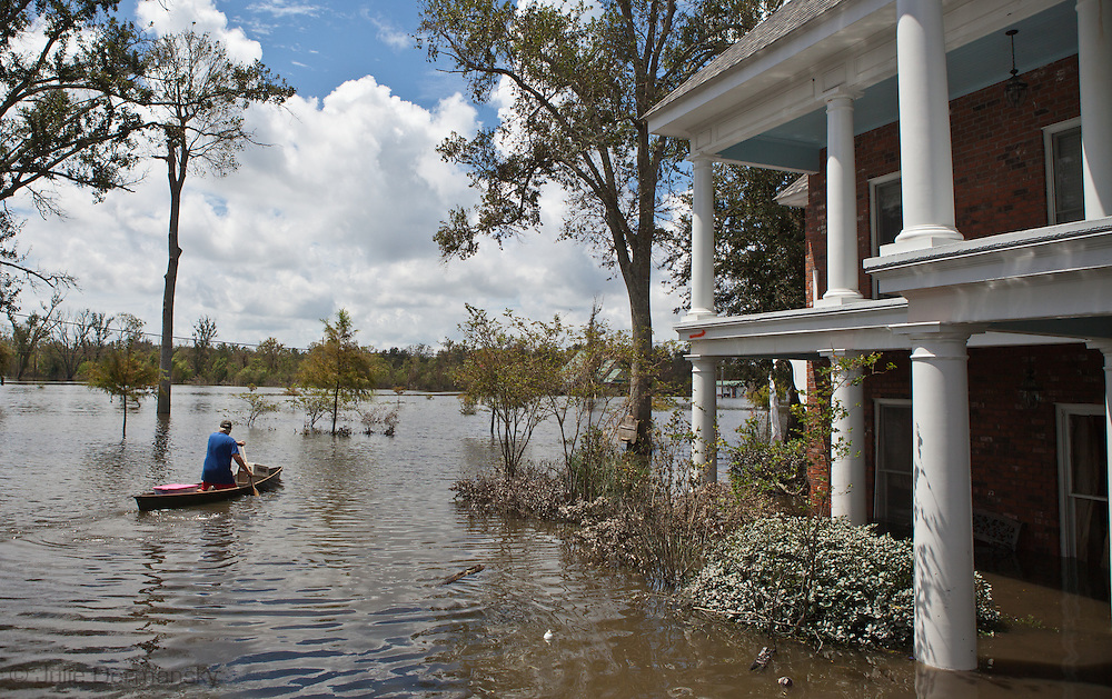 September 2,  Scarsdale, LA in Plaquemines Parish on the East Bank of the Mississippi River, Don Duplantier in a pirogue riding away from his home. Scarsdale is outside of the storm protection system created by the giant wall that was constructed after Hurricane Katrina. Don Duplantier's home took on 12 ft. of water from Isaac, a category one hurricane.