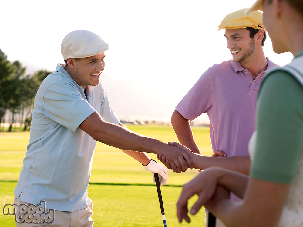 Yong golfers shaking hands on course