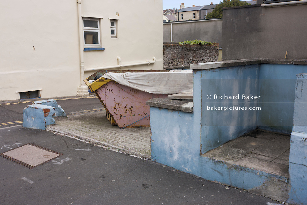 Urban backstreet landscape of a skip and fading walls in seaside town of Weston-super-Mare in north Somerset.