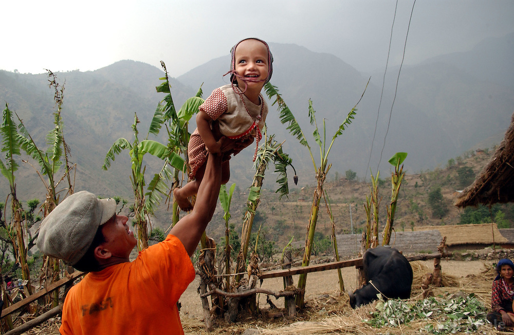 """RUKUM DISTRICT, NEPAL, APRIL 20, 2004:  A Maoist  insurgent holds a baby at a village in Rukum district April 20, 2004. Analysts and diplomats estimate there about 15,000-20,000  fighters, including many women, backed by 50,000 """"militia"""".  Though the movement uses violence to acheive theri goals, many say that the positive effects in the areas that are dominated by them are that there is there is less abuse because people are not allowed to drink alcohol or have mulitple wives.  they collect taxes and have set up civil administrations, and """"people's courts"""" to settle rows. They also raise money by taxing villagers and foreign trekkers. Though young, they are fearsome fighters and  specialise in night attacks and hit-and-run raids. They are tough in Nepal's rugged terrain, full of thick forests and deep ravines and the 150,000 government soldiers are not enough to combat this growing movement that models itself after the Shining Path of Peru. (Ami Vitale/Getty Images)"""
