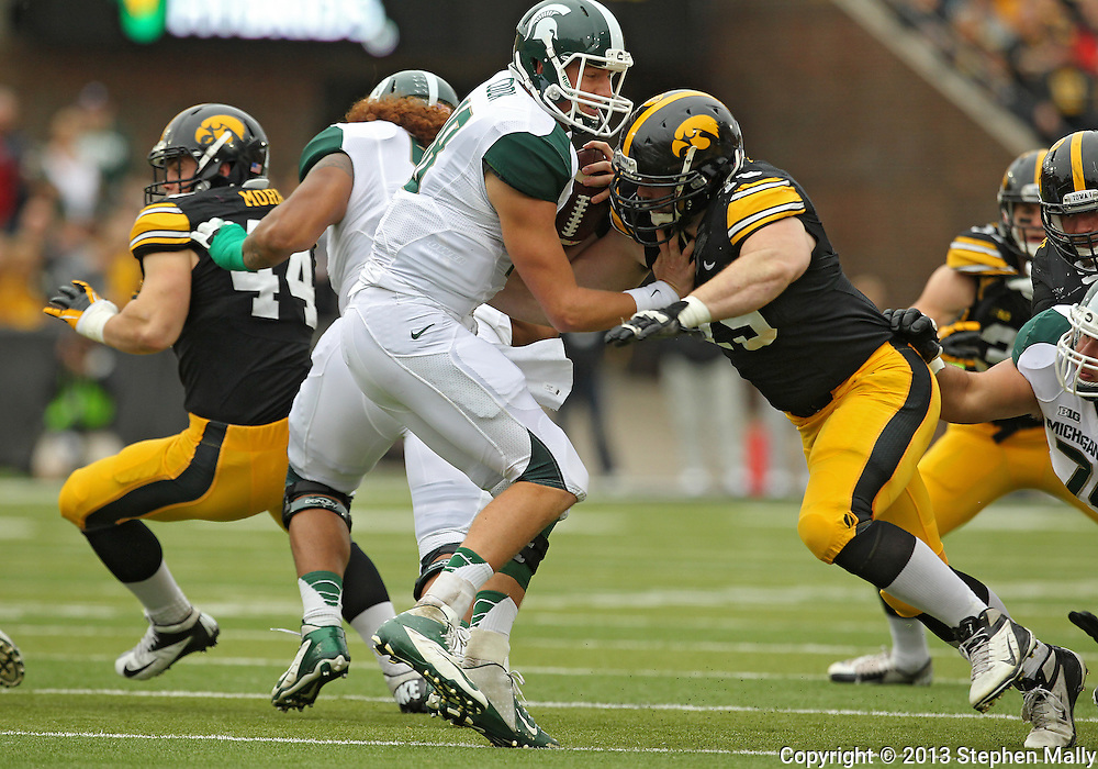 October 6 2013: Michigan State Spartans quarterback Connor Cook (18) is hit by Iowa Hawkeyes defensive lineman Dominic Alvis (79) during the first quarter of the NCAA football game between the Michigan State Spartans and the Iowa Hawkeyes at Kinnick Stadium in Iowa City, Iowa on October 6, 2013. Michigan State defeated Iowa 26-14.