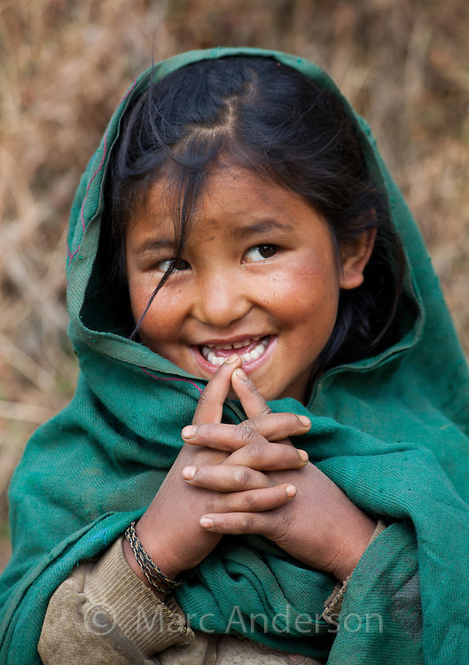 Portrait of a little Nepalese girl wearing a green shawl and smiling, Helambu Region, Nepal