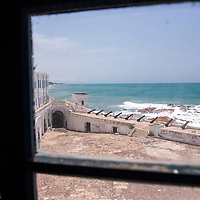 View through a window of historic cannons and the Atlantic Ocean at the Cape Coast Castle, a UNESCO World Heritage Site located along the Gold Coast of Ghana.