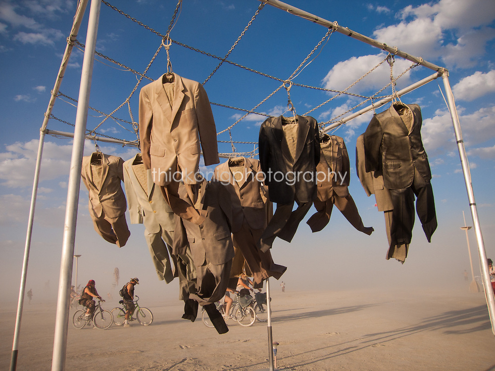 Mens suits hanging blowing in the wind art installation at Burning Man Festival, with blue sky and puffy white clouds, Black Rock City.