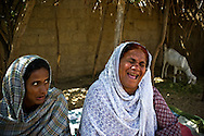 Rehana (left) and her cousin Sharifa (right) have both been dai for over 12 years and carried on their family tradition having learnt by watching their mothers and aunties. <br /> They say they want to help women who can't afford hospital care and offer their deliveries for free. <br /> Most dai lie about the fees they charge and most women become dai to earn an extra income. Karachi, Pakistan, 2011