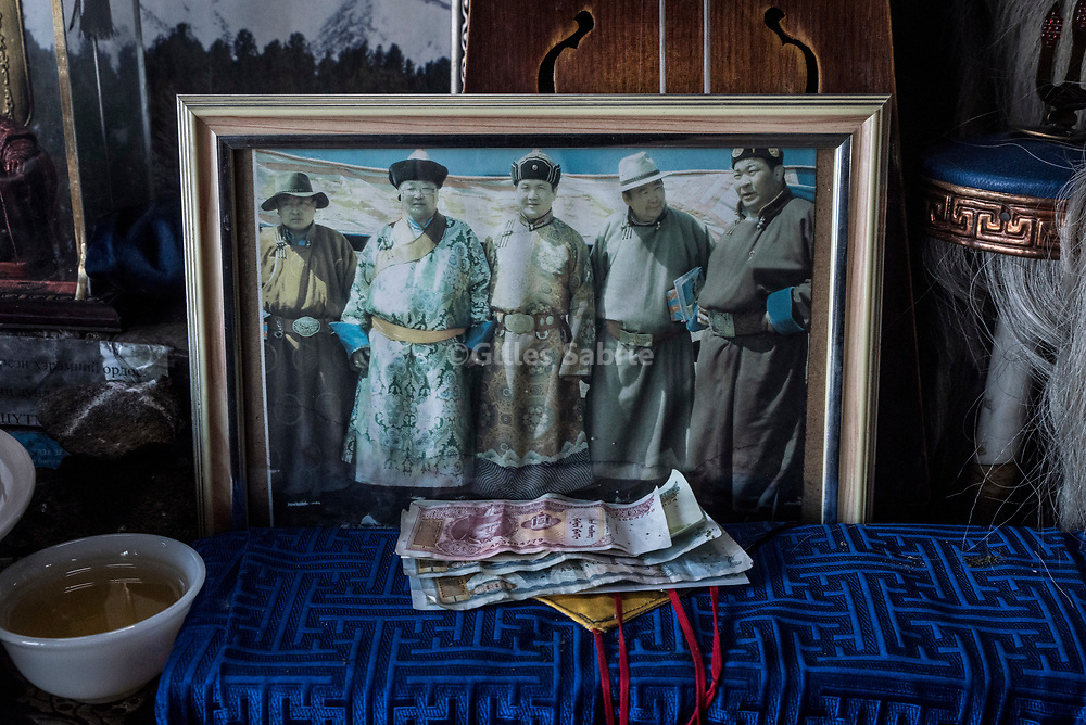 Ulaanbaatar, MONGOLIA, April 3rd 2017<br /> In the prayer room of master shaman Byambadorj a framed picture of himself (second from left) with former Mongolia president Nambar Enkhbayar (3rd from left) and Badmaanyambuu Bat-Erdene (first from right) Mongolia former National wrestling champion and current parliament member, has been placed on the altar. Shamanism is increasingly popular in Mongolia and mixes with politics. Many members of parliaments practice shamanism, and even some being shaman themselves.<br /> Gilles Sabri&eacute; for 1843
