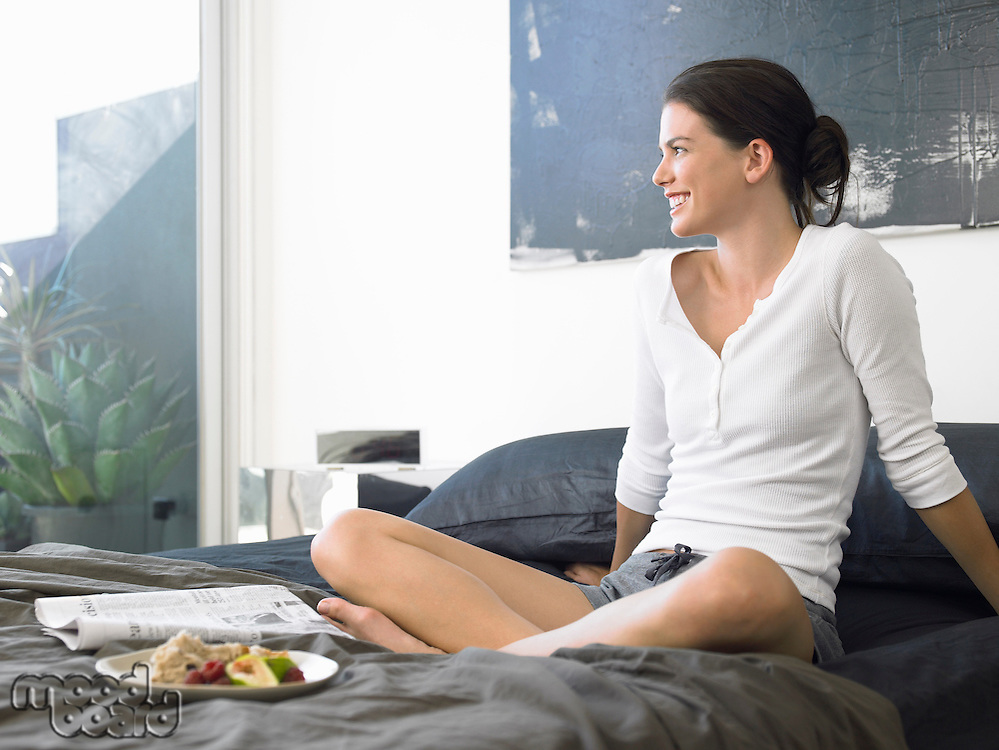 Woman sitting on bed with food and paper