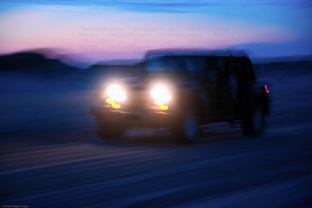 SUV riding off road at night.